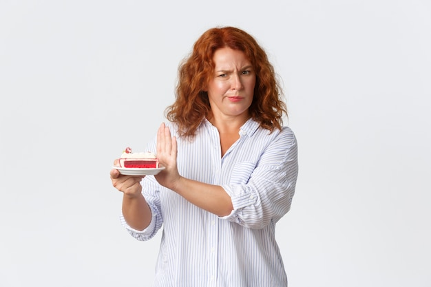 Fronçant les sourcils et grimaçant rousse femme d'âge moyen tenant le gâteau, montrant le geste de refus