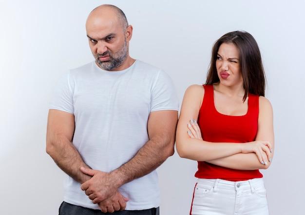 Fronçant les sourcils homme couple adulte gardant les mains ensemble à la recherche et femme debout avec une posture fermée en le regardant avec un œil fermé