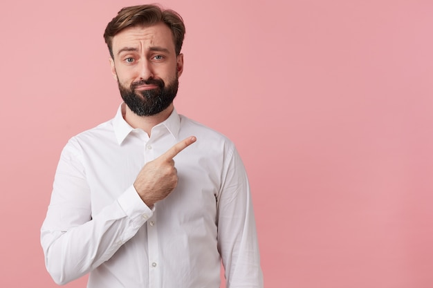 Fronçant les sourcils, un homme malheureux veut attirer votre attention en pointant du doigt sur l'espace de copie à droite, isolé sur fond rose.