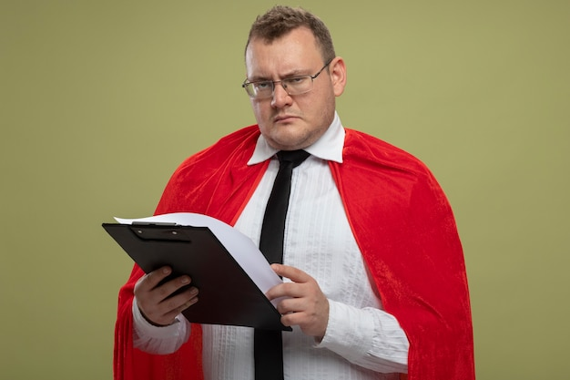 Fronçant les sourcils homme de super-héros adultes en cape rouge portant des lunettes et une cravate tenant le presse-papiers à l'avant isolé sur mur vert olive