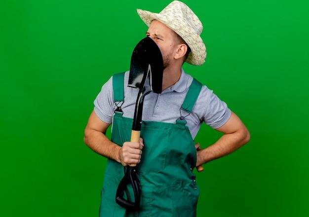 Fronçant les sourcils jeune beau jardinier slave en uniforme et hat holding spade devant le visage et râteau derrière le dos à côté