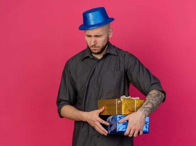Fronçant les sourcils jeune beau mec de fête slave portant chapeau de fête tenant des paquets-cadeaux avec les yeux fermés isolés sur fond cramoisi avec espace copie