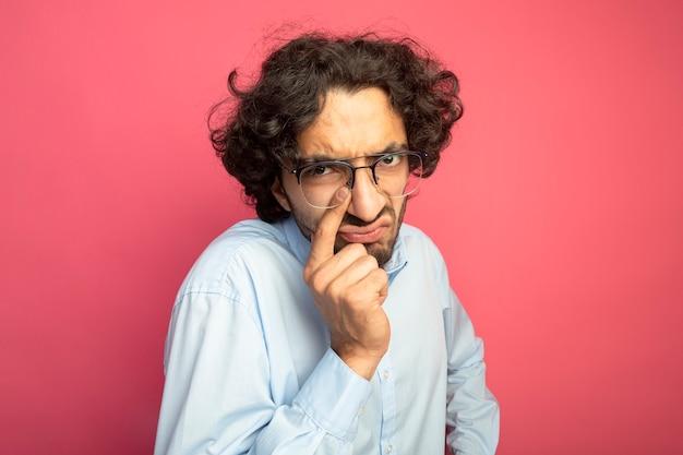Fronçant les sourcils jeune bel homme caucasien portant des lunettes mettant le doigt sur le nez isolé sur mur cramoisi avec espace copie