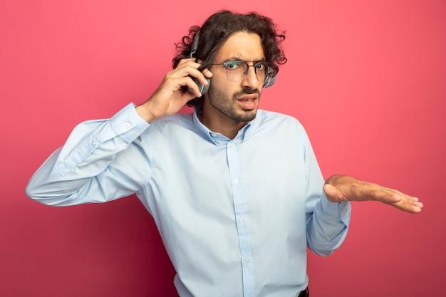 Fronçant les sourcils jeune bel homme portant des lunettes et des écouteurs en regardant les écouteurs à l'avant en gardant la main dans l'air expliquant quelque chose d'isolé sur le mur rose