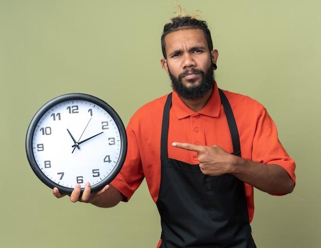 Fronçant les sourcils jeune coiffeur en uniforme tenant et pointant sur l'horloge regardant à l'avant isolé sur mur vert olive