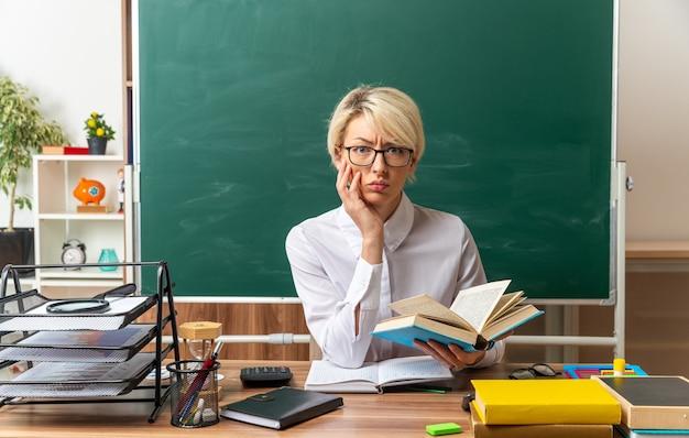 Fronçant les sourcils jeune enseignante blonde portant des lunettes assis au bureau avec des outils scolaires en classe tenant un livre ouvert en gardant la main sur le visage en regardant la caméra
