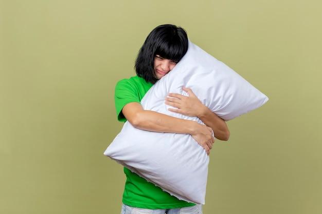 Fronçant les sourcils jeune femme malade hugging oreiller regardant vers le bas isolé sur mur vert olive