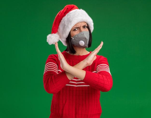 Fronçant les sourcils jeune fille portant bonnet de noel et masque de protection ne faisant aucun geste isolé sur un mur vert avec espace copie