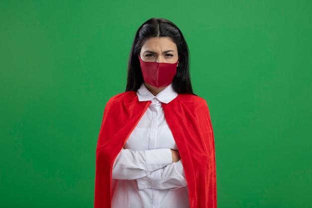 Fronçant les sourcils jeune fille de super-héros caucasien portant un masque debout avec une posture fermée isolé sur un mur vert avec espace copie