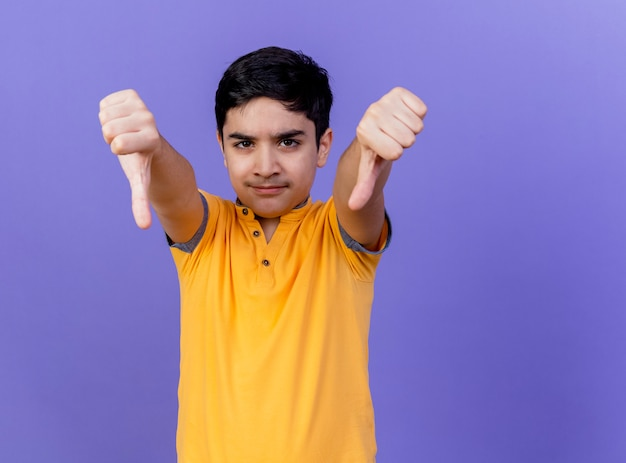 Fronçant les sourcils jeune garçon caucasien montrant les pouces vers le bas isolé sur un mur violet avec copie espace