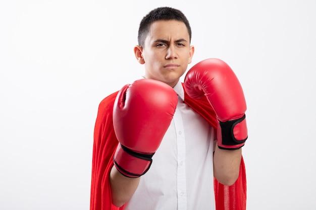 Fronçant les sourcils jeune garçon de super-héros en cape rouge portant des gants de boîte regardant la caméra faisant le geste de boxe isolé sur fond blanc avec espace de copie