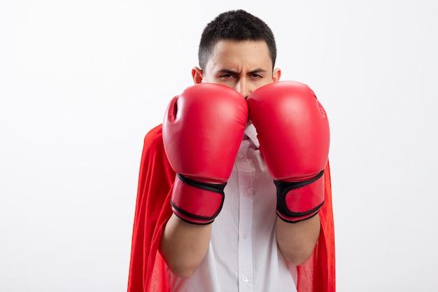 Fronçant les sourcils jeune garçon de super-héros en cape rouge portant des gants de boîte regardant la caméra en gardant les mains devant le visage isolé sur fond blanc avec espace copie