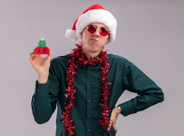 Fronçant les sourcils jeune homme blond portant bonnet de noel et lunettes avec guirlande de guirlandes autour du cou tenant un jouet d'arbre de noël avec date regardant la caméra en gardant la main sur la taille isolé sur fond blanc