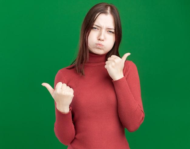 Fronçant les sourcils jeune jolie fille pointant sur les côtés avec des joues gonflées isolé sur mur vert avec copie espace