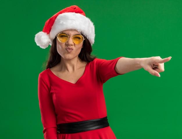 Fronçant les sourcils jeune jolie fille portant bonnet de noel et lunettes à la recherche et pointant sur le côté isolé sur fond vert