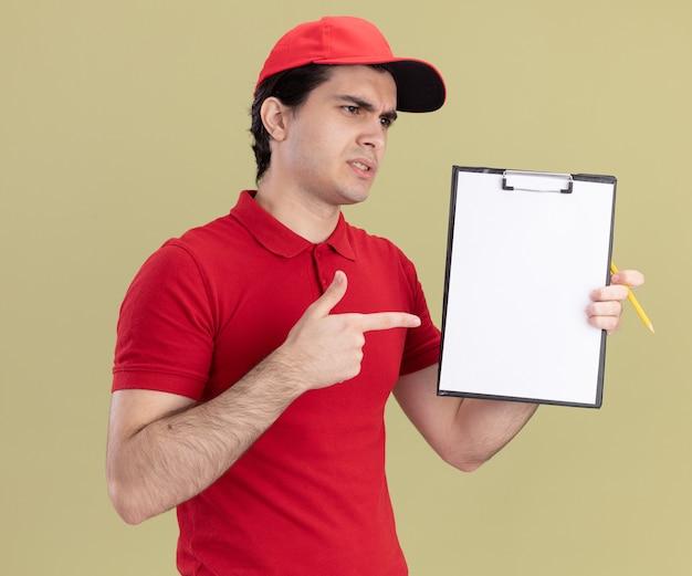 Fronçant les sourcils jeune livreur caucasien en uniforme rouge et casquette montrant le presse-papiers