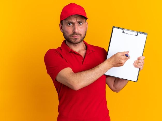 Fronçant les sourcils jeune livreur caucasien en uniforme rouge et casquette montrant le stylo pointant le presse-papiers dessus
