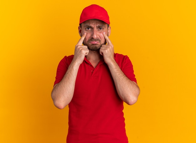 Fronçant les sourcils jeune livreur caucasien en uniforme rouge et casquette regardant la caméra pincer les lèvres en gardant les doigts sous les yeux isolés sur un mur orange avec espace de copie