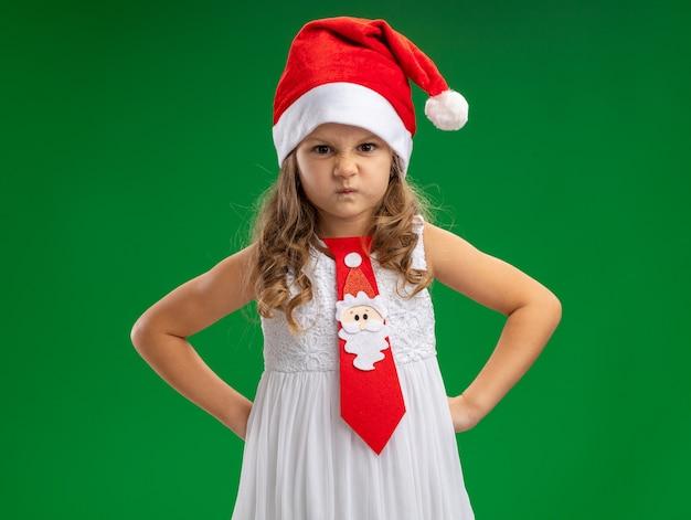 Fronçant les sourcils petite fille portant un chapeau de noël avec une cravate mettant les mains sur la hanche isolé sur mur vert