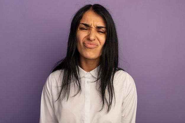 Fronçant les sourcils avec les yeux fermés jeune belle fille portant un t-shirt blanc isolé sur violet