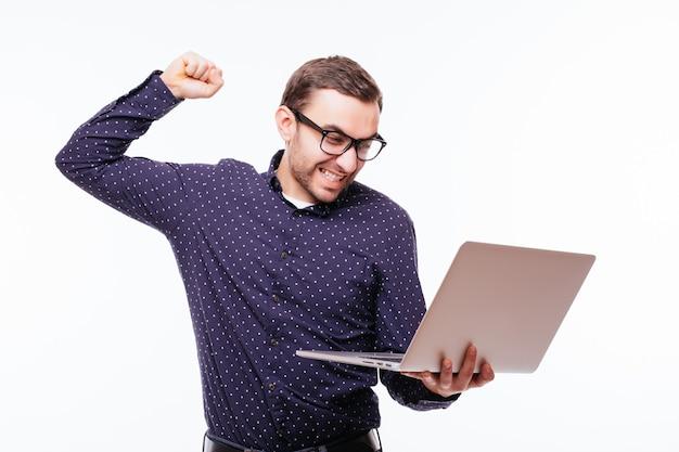 Froncer les sourcils sérieux homme caucasien en costume à l'aide d'un ordinateur portable isolé sur blanc