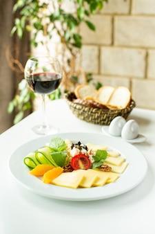 Un front close up view tranches de fruits frais mûrs avec du vin rouge sur le bureau blanc