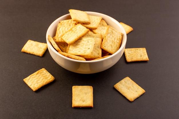 Un front fermé vue chips salées savoureux craquelins fromage à l'intérieur de la plaque blanche sur l'obscurité