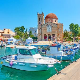 Front de mer avec l'église ekklisia isodia theotokou dans la ville d'égine et les bateaux de pêche amarrés, l'île d'égine, grèce