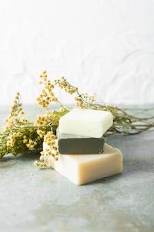 Front view bouquet de fleurs de soin de la peau à côté de savons