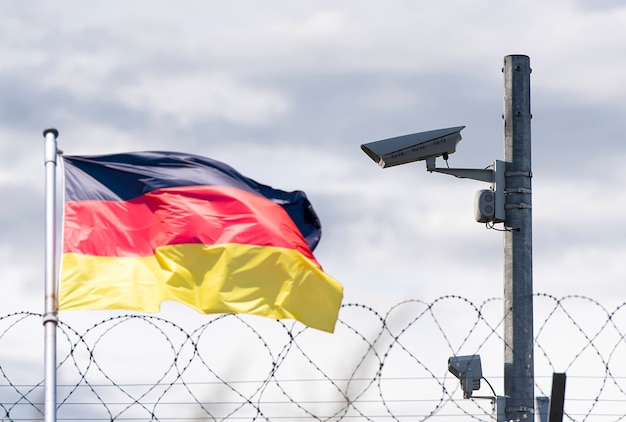 Frontière de l'allemagne, ambassade, caméra de surveillance, fil de fer barbelé et drapeau de l'allemagne, photo de concept