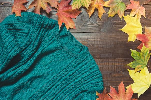 Frontière d'automne avec pull vert confortable, feuilles colorées sur planche de bois vue de dessus.