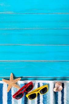 Frontière de fond de plage d'été, lunettes de soleil, serviette, étoile de mer, terrasse en bois bleu, espace copie
