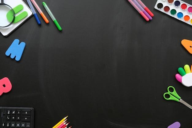 Frontière avec fournitures scolaires et place pour le texte sur fond de tableau noir.