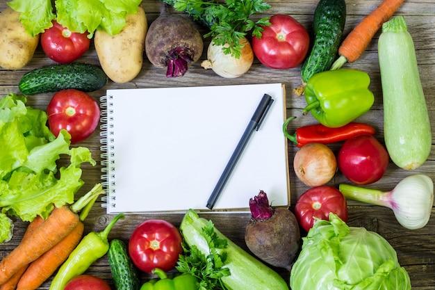 Frontière de légumes juteux, bloc-notes blanc vierge avec espace copie et stylo, vue de dessus.