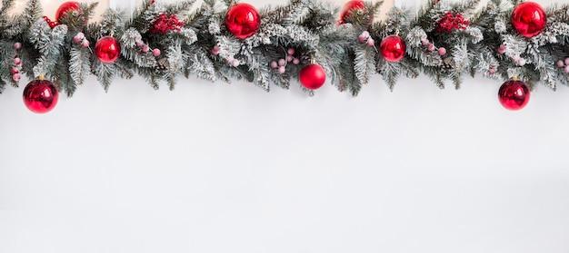 Frontière de noël - branches d'un arbre de noël avec des décorations rouges isolés sur une bannière horizontale blanche