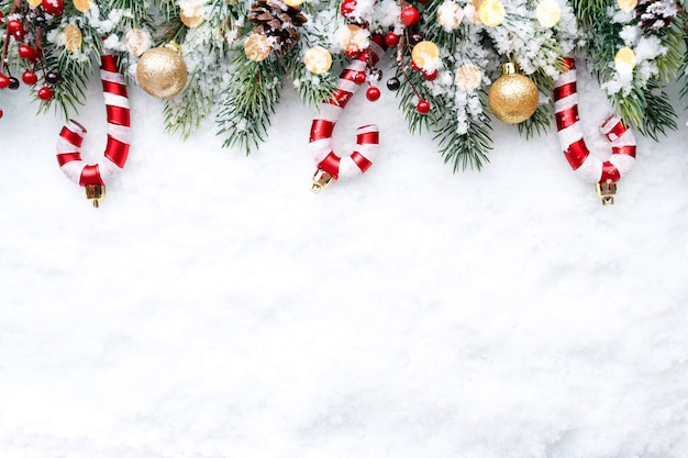 Frontière de noël - branches d'arbres avec des boules dorées, des bonbons et des cônes sur la neige