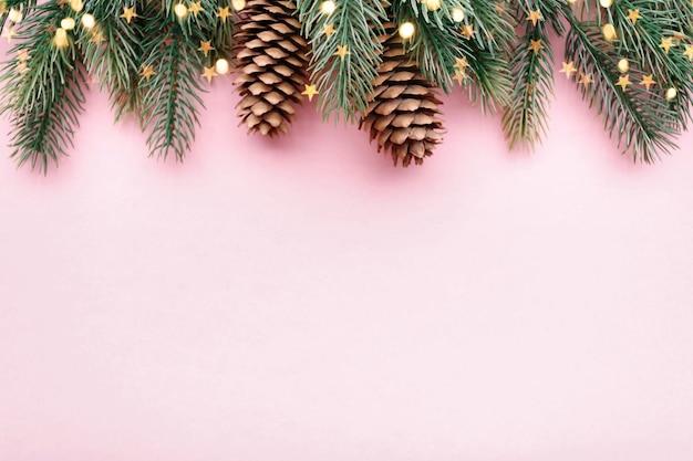 Frontière de noël avec des branches de sapin et des cônes de conifères sur fond rose pastel, espace copie