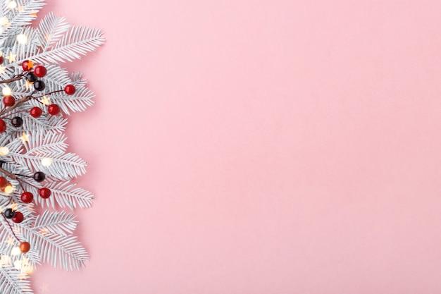 Frontière de noël avec des branches de sapin, rowan et lumières dorées sur fond rose pastel, espace copie