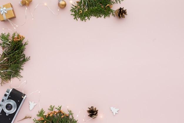 Frontière de noël. cadre de noël avec des cadeaux, branches de sapin sur fond rose pastel. mise à plat, vue de dessus, espace de copie