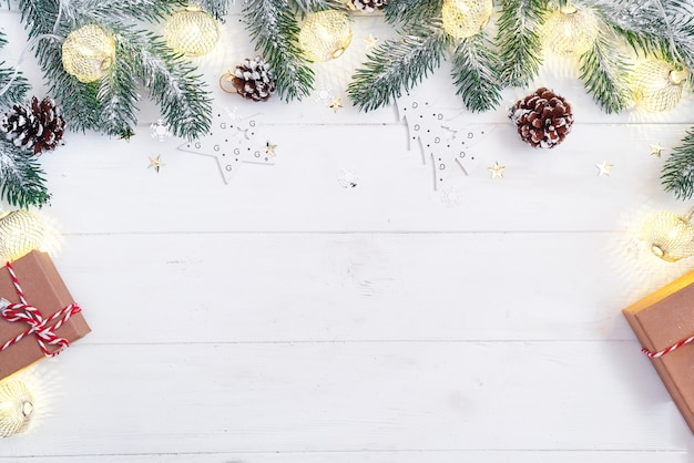 Frontière de noël isolée sur blanc, composée de branches de sapin fraîches, de lumières et de cadeaux.
