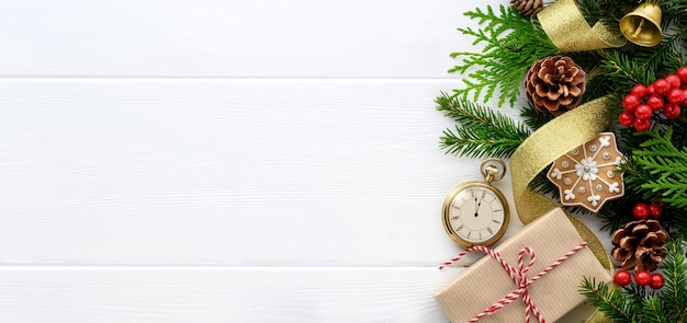 Frontière de la saint-sylvestre. branches de sapin avec décorations de noël d'horloge de style rétro et cadeau sur fond de bois blanc. derniers instants avant noël ou nouvel an. vue de dessus. espace de copie