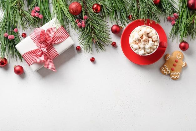 Frontière de vacances de noël avec cadeau, café, pain d'épice, branches à feuilles persistantes sur fond blanc. carte de voeux de vacances de noël avec espace de copie. vue de dessus, mise à plat.