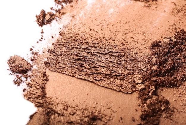 Frottis de fard à paupières doré écrasé. isolé sur blanc. cosmétiques professionnels. fond de cosmétiques abstrait.