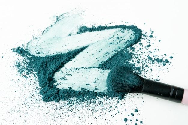 Frottis de fard à paupières vert écrasé comme échantillon de produit cosmétique isolé sur fond blanc avec espace de copie.