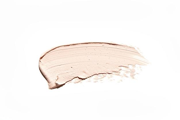 Frottis de fond de teint crémeux maquillage beige isolé sur fond blanc. échantillon de cosmétiques pour la peau, coup de pinceau crème brun clair. estompez la texture du produit bronzant pour le visage ou du fond de teint bb
