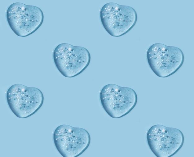 Les frottis de gel cosmétique ressemblent à un motif de coeur fond bleu propre avec espace de copie