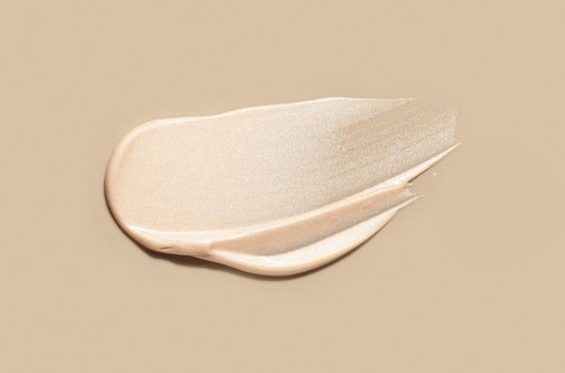 Frottis de maquillage liquide beige clair de fard à joues lumineux crémeux sur fond beige