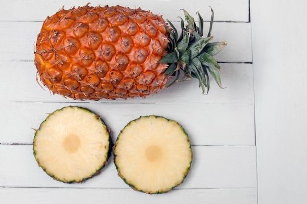 Fruit d'ananas açores frais isolé sur un fond en bois blanc.