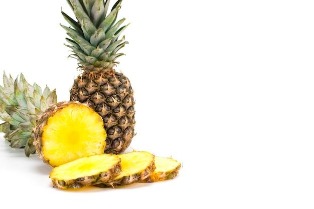 Fruit d'ananas avec des tranches isolé sur blanc