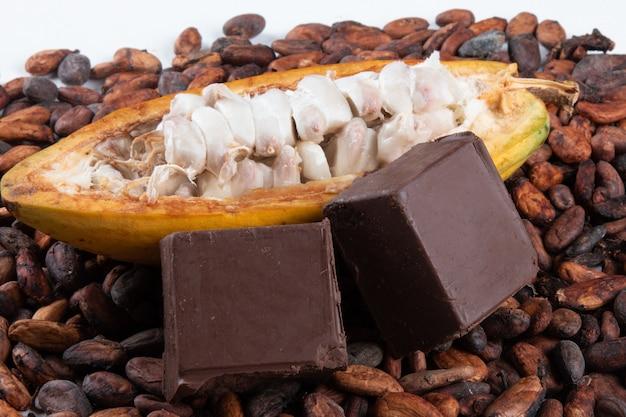 Fruit de cacao coupé avec des fèves de cacao crues et des morceaux de chocolat